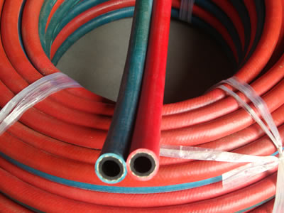 There is a roll of twin welding hoses packed by plastic rope.